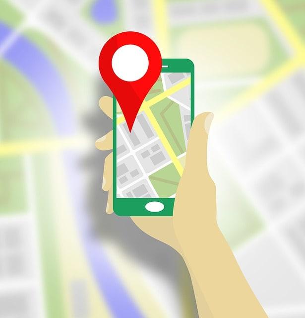 Pessoa segurando um smartphone. O smartphone apresenta um mapa com um local de destino marcado. Analogia com domínio de site.